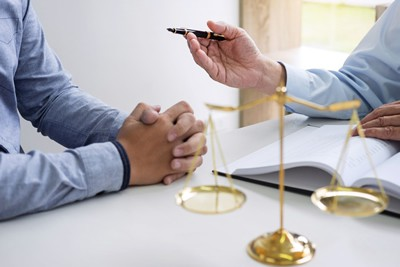 Business lawyer sitting down with a client at a desk while holding a pen