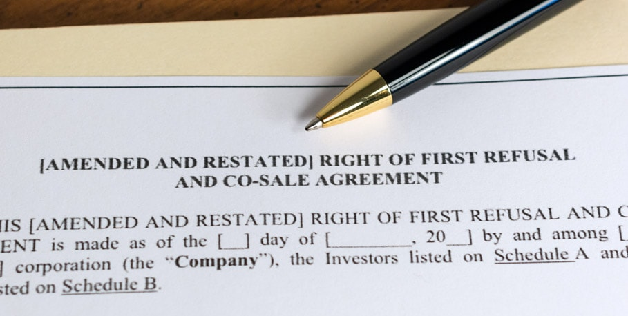 Yellow folder with a pen on top and a legal document that's titled amended and restated right of first refusal and co-sale agreement