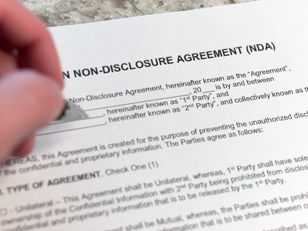 Pen about to sign a Non-Disclosure Agreement form with legal language and spaces for each party to fill in information